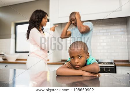 Parents arguing in front of son in the kitchen