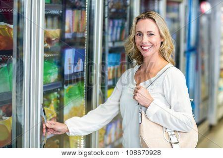 Side view of smiling woman opening supermarket fridge