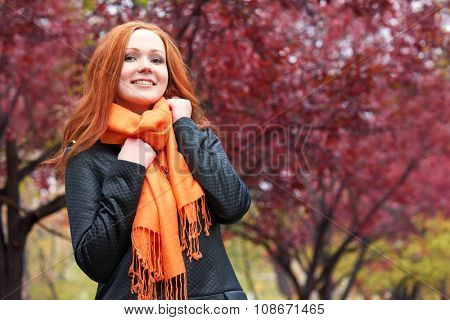 redhead girl in city park on red tree background, fall season