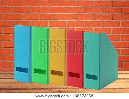 Colorful Office Folders On Wooden Table Over Orange Brick Wall Background