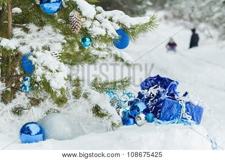 Christmas snowy pine tree decorated with shiny baubles and two children sledging on snow covering