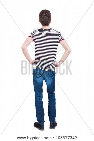 Back view of man in jeans. Standing young guy. Rear view people collection.  backside view of person.  Isolated over white background. The guy in the striped shirt with hands on hips standing.
