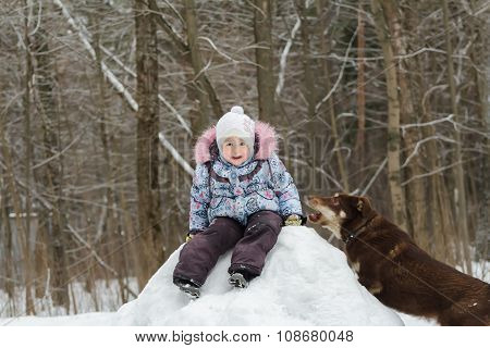 Little girl playing in winter forest on snowy hill with her pet dog