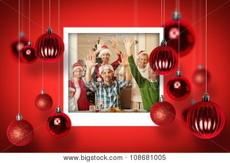 Happy extended family in santa hat cheering at camera against christmas photographs