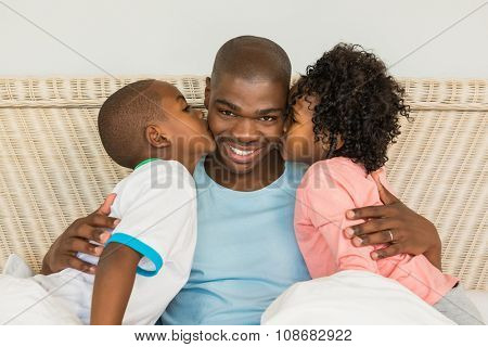 Children kissing father in bed at home