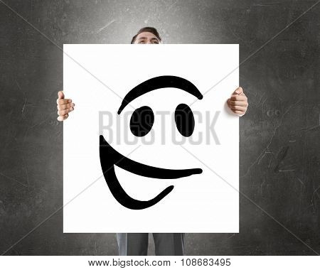 Businessman holding and hiding behind card with smiley face emoticon