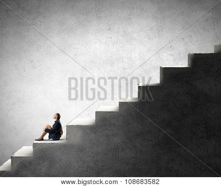Bored young businesswoman sitting alone on ladder steps