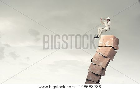 Businessman sitting on big stack of carton boxes and looking in spyglass