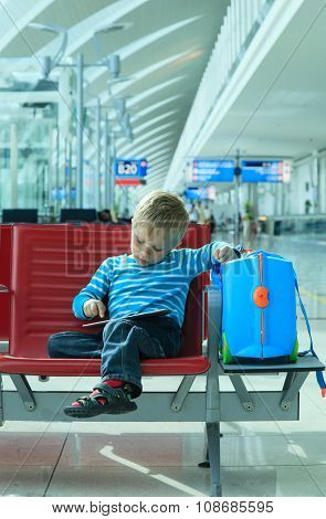 little boy with touch pad waiting in the airport