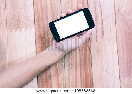 Part of hand typing on smartphone on wooden desk