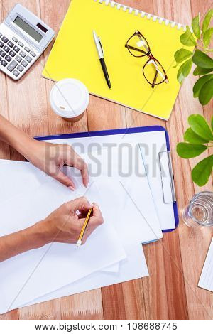 Part of hands taking notes on wooden desk