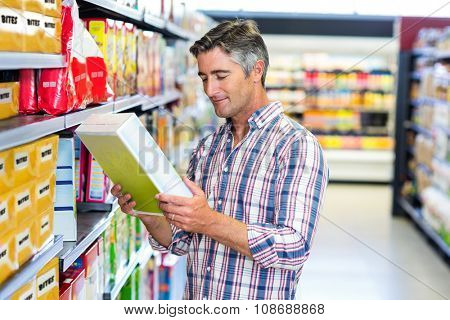 Man reading nutritional values at supermarket