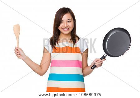 Asian Housewife holding up with wooden ladle and frying pan
