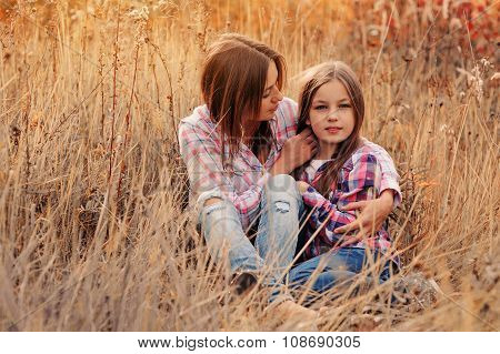 Happy Mother And Daughter On Cozy Walk On Sunny Field