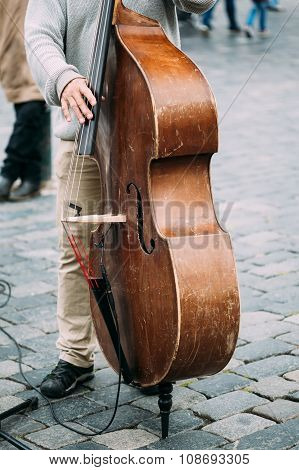 Street Busker performing jazz songs. Close up of contrabass.
