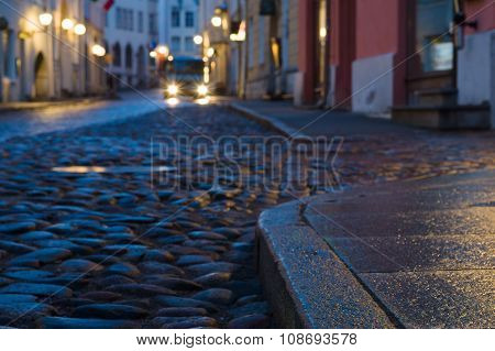 Early Morning Old Town Street With Car Glowing Headlights