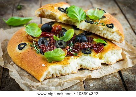 Piece Of Italian Focaccia Bread With Black Olives, Dried Tomatoes And Basil