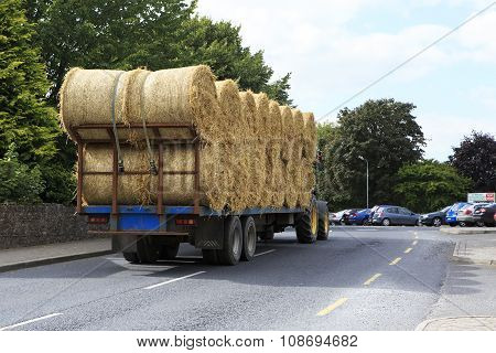 Tractor transporting straw bales in irish countryside