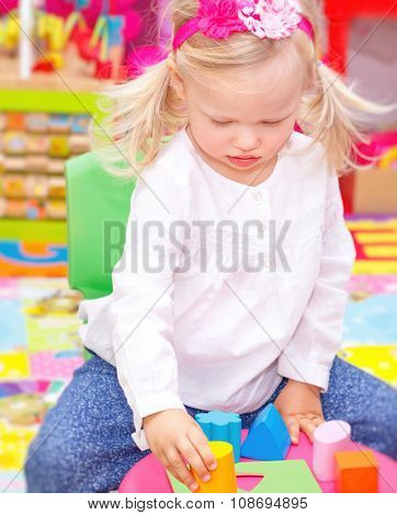 Cute adorable blond baby girl having fun in daycare, playing with colorful toys in playroom, happy healthy childhood