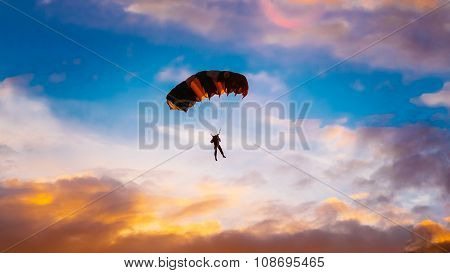 Skydiver On Colorful Parachute In Sunny Sunset Sunrise Sky