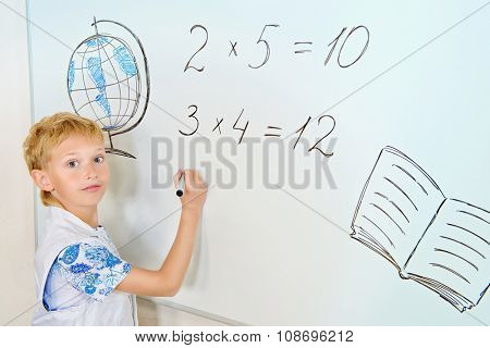 Schoolboy performs the tasks at the blackboard in the classroom. Education.