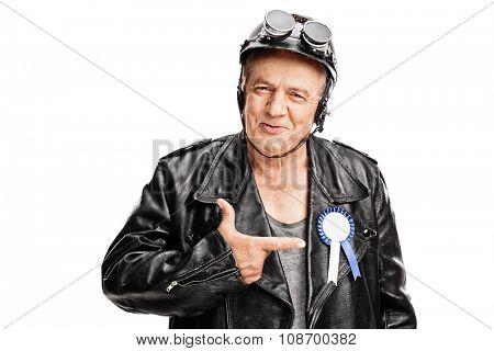 Joyful senior biker pointing towards a blue award ribbon on his black leather jacket isolated on white background