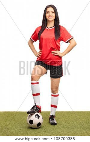 Full length portrait of a young female football player stepping over a ball on a grass field and looking at the camera isolated on white background