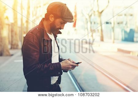 Half length portrait of bearded male with retro style using cell telephone while standing outdoors