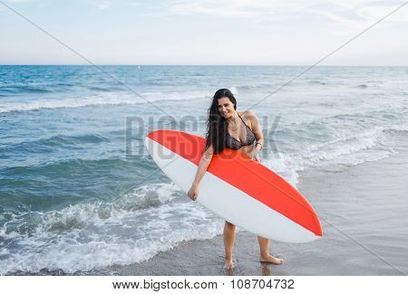 Full length portrait of a young female surfer standing on the coast while taking break after surfing