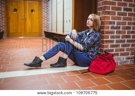 Worried student sitting on the floor against the wall at the university
