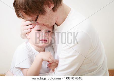 father comforting son in tears