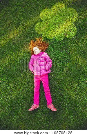 Child Lying On The Green Grass In Park Under Lighting Cloud In Sunset Light.