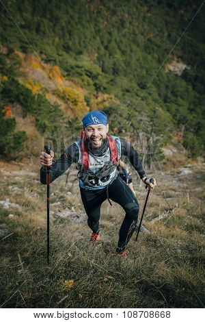 joyful young athlete climbs a mountain with nordic walking poles
