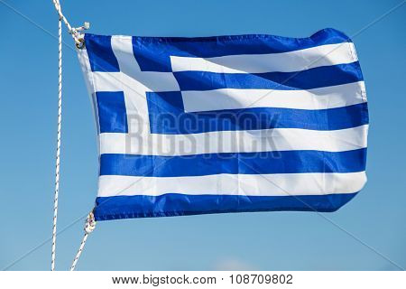 Photo of national blue and white striped Greece flag flutters in the wind against of blue clear sky. Summer time