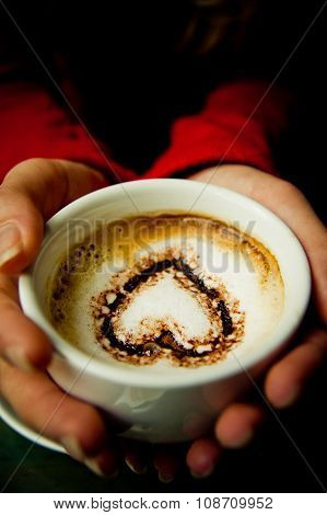 Hands Holding Coffee with Cocoa Heart in the Cup