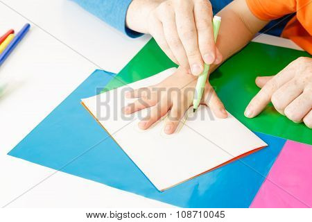 father outdrawing child hand