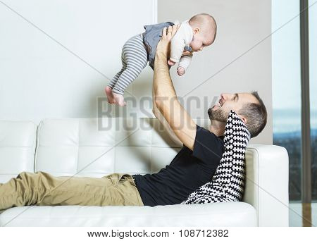 Father with baby on the sofa taking good time