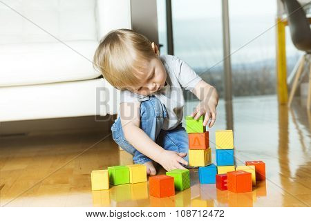 kid playing toy blocks inside his house