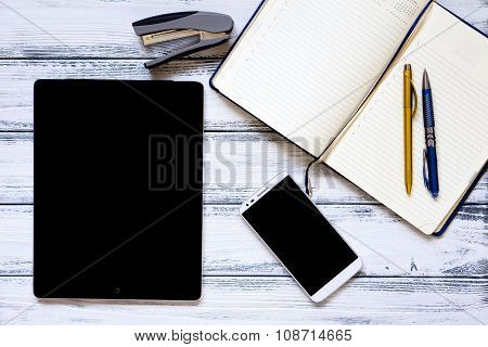 Modern Workplace With Laptop, Golden And Silver Pen, Smartphone, Notepad And Stapler On White Wooden