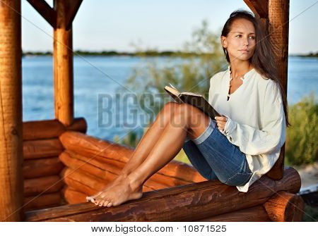 Young Pensive Lady With Book In Summerhouse On Sunset