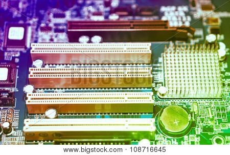 Techno Gradient Violet, Red And Green Colors Background Of Computer Motherboard With Blur Effect