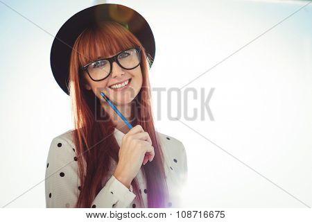 Smiling hipster woman posing with a pencil in a bright room