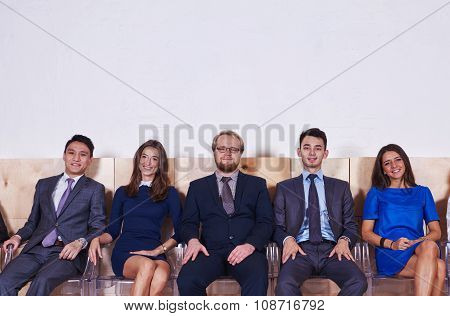 Multi ethnic group of prosperous workers waiting for start business meeting