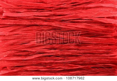 Background - red paper raffia strips placed in parallel lines.
