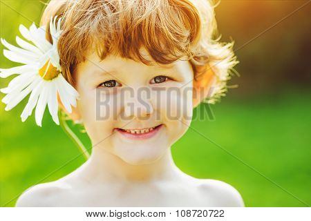 Child With Camomile In His Hair In Summer Park.