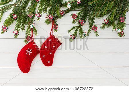 Christmas Background. Red Christmas Socks On White Wooden Background With Decorated Christmas Fir Tr