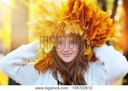 Beautiful Red-haired Young Girl With A Wreath Of Yellow And Red Leaves On The Head