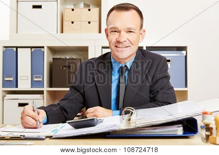 Finance clerk sitting at his desk with files and a calculator