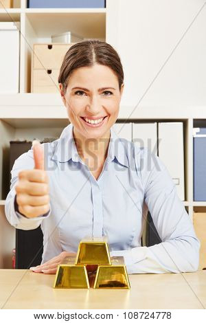 Happy business woman with gold bars on the table holding thumbs up