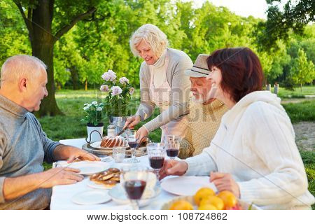 Family with senior people eating cake at birthday party in a garden